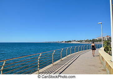 Woman walking at the coastal promenade