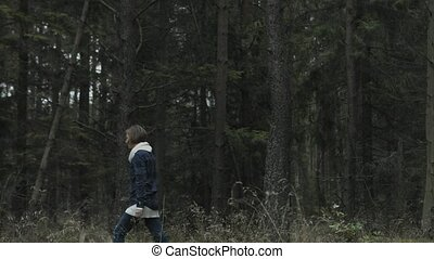 Young woman walking away on a forest, alone. She is resting in the nature. Woman walks from right side to left.