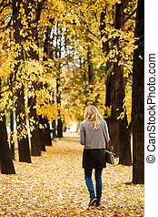 Woman walking away in autumn park with golden trees
