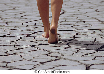 Woman walking barefoot across cracked earth, low section