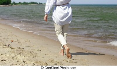 woman walking barefoot along beach - people and leisure...