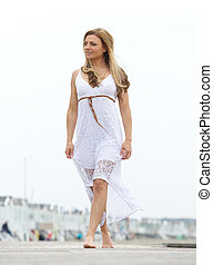 Woman walking barefoot in white dress outdoors