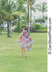 Woman walking barefoot on a tropical green field. Bali island, Indonesia. Nusa Dua park.