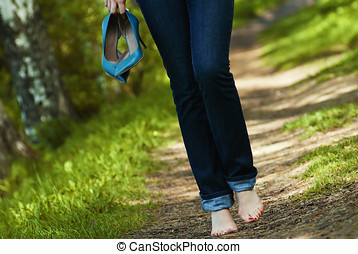 Woman walking barefoot on grass.