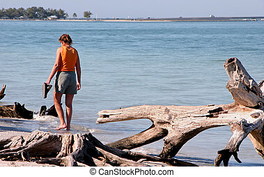 woman walking barefoot on beach Sanibel Florida