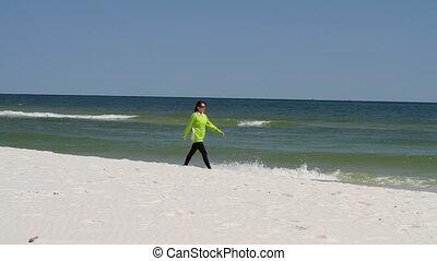Woman Walking Beach - Woman walks along a sandy beach...