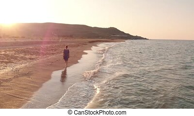 Woman walking by the coastline - Young woman in dress walk...