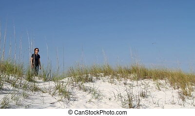 Woman Walking Down Dune - Mature woman walks over a sand...