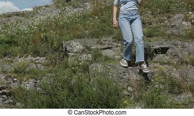 woman walking down rocks