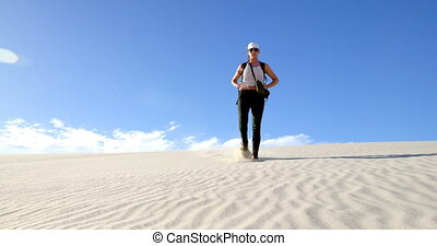 Woman walking down the sand dune in desert 4k - Woman...