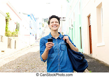 Woman walking down the street with cell phone and bag