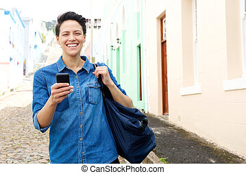 Woman walking down the street with mobile phone and bag