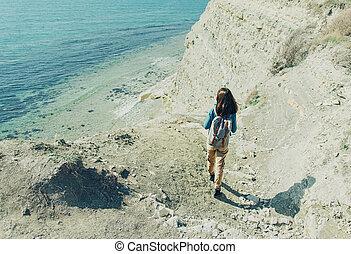 Woman walking down to the sea