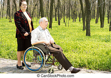 Woman walking her husband in his wheelchair
