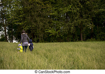 Woman walking her two children through a field