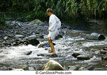 Woman walking in a stream