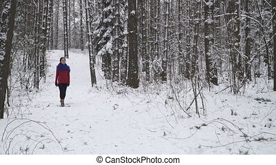 woman walking in a winter forest
