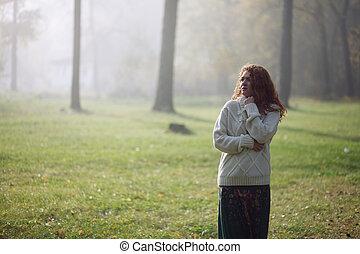 Woman walking in foggy forest