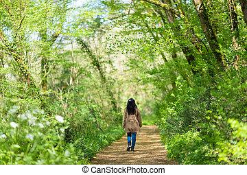 Woman walking in green forest
