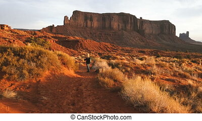 woman walking in Monument Valley taking photos with smartphone.