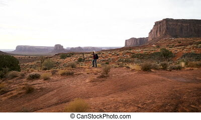 woman walking in Monument Valley with red rocks overview....