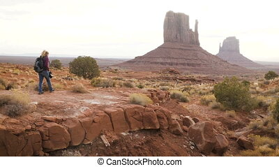 woman walking in Monument Valley with red rocks overview.
