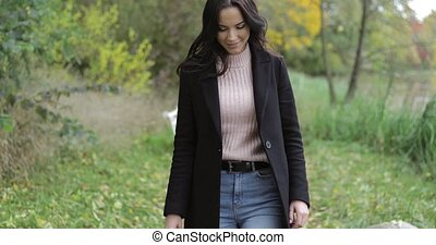 Woman walking in park - Attractive woman in black jacket and...