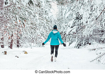Woman walking in snow through forest