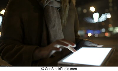 Woman walking in the evening street and using tablet computer