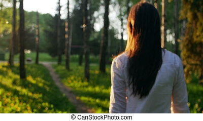 Woman walking in the forest at sunset. Slow motion