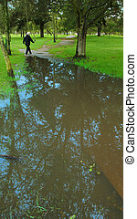Woman walking in the La Carolina park next to a large puddle of water after the rain. Quito - Ecuador