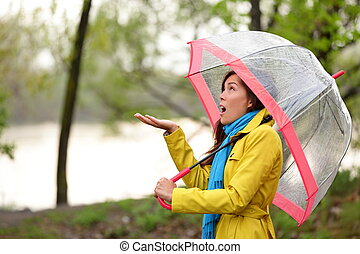 Woman walking in the rain in Autumn forest