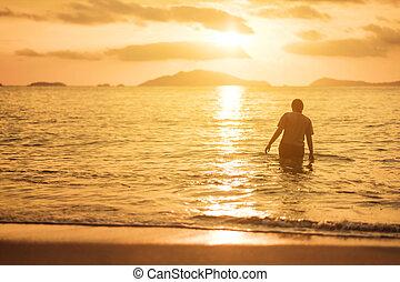 Woman walking in the sea in sunset