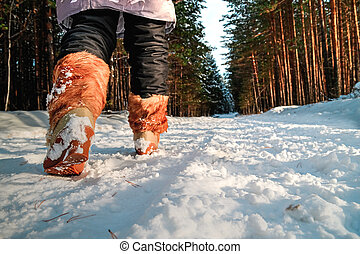 Legs of a woman in warm boots on the snow.