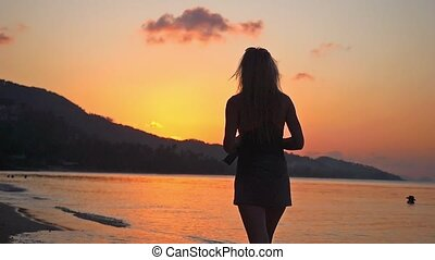 Woman walking in tropical beach at sunset in slow motion.