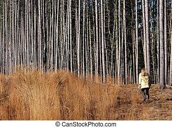 Woman walking in wooded meadow.
