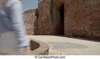 Woman walking into a european castle building