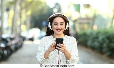 Woman walking listening to music slow motion - Front view of...