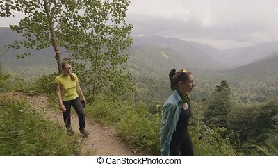 Woman walking mountain trail with beautiful landscape while hiking tour