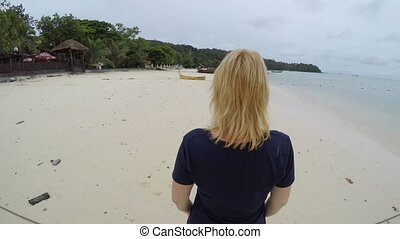 Woman walking on a beach and flirting