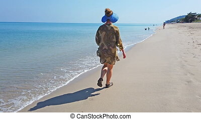 Woman walking on a beach with yellow sand and sea water. 4K...