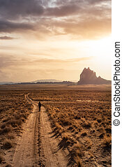 Woman walking on a dirt road in the dry desert