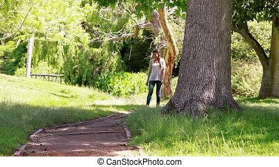 Woman walking on a footpath in a park