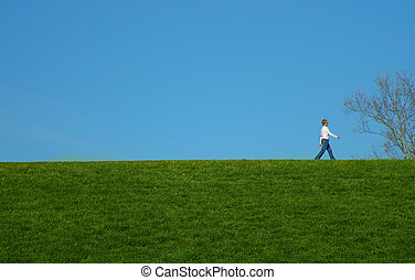 Woman walking on a hill with green grass and blue sky