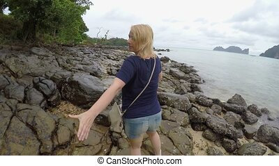 Woman walking on a rocky beach holding hands