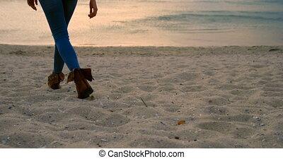 Woman walking on beach 4k - Low section of woman walking on...