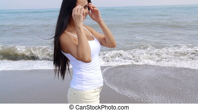 Woman Walking on Beach and Smiling at Camera