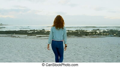 Woman walking on beach at dusk 4k
