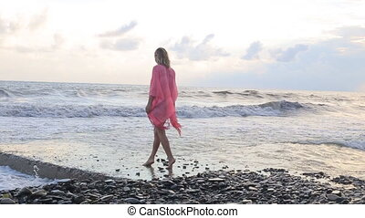 Woman walking on beach at sunset in summer.