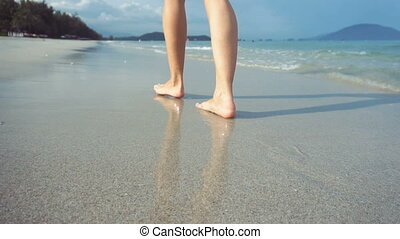 Woman walking on beach barefoot at sunset. Female strolling on sand near sea.